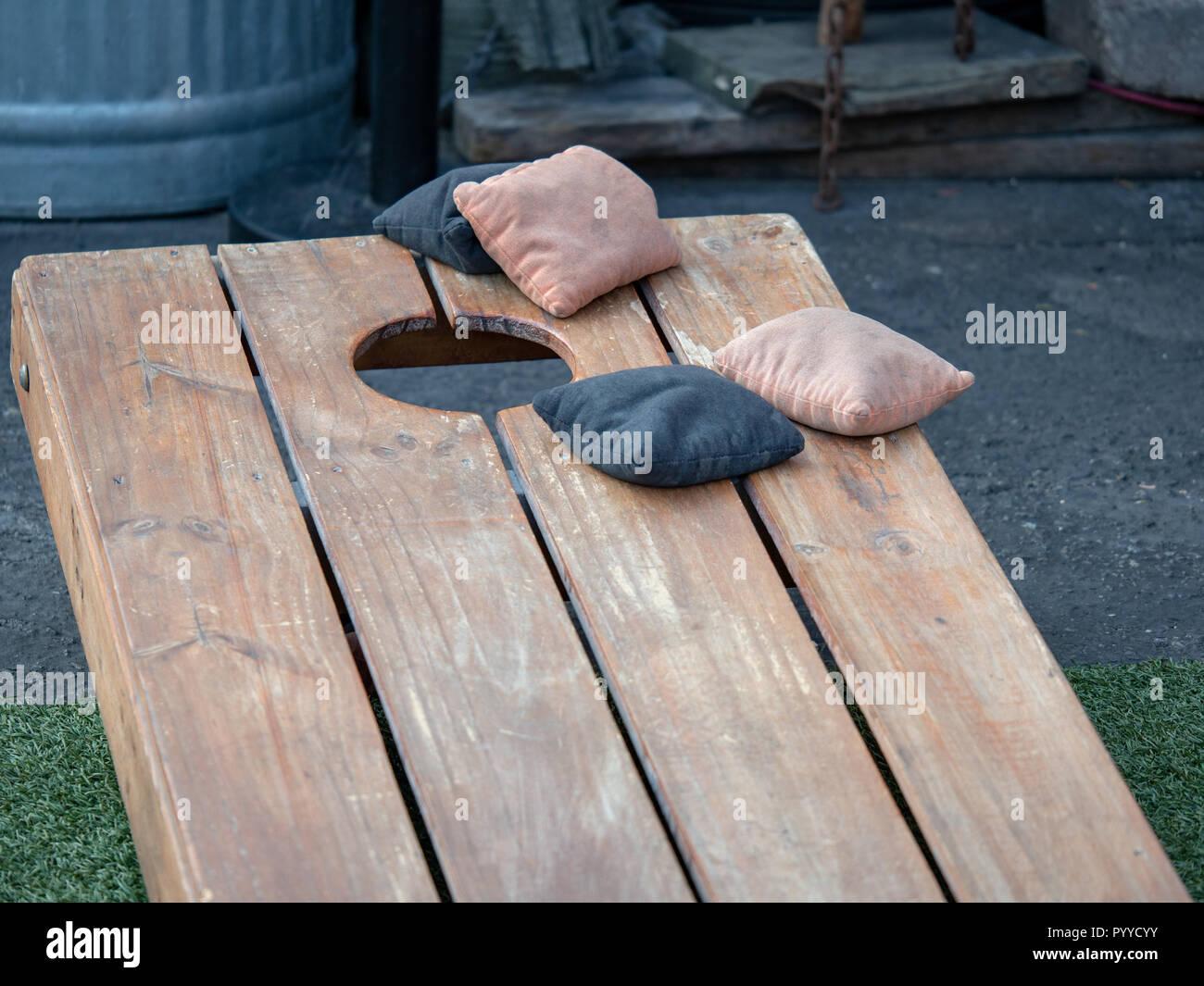 Competing black and beige beanbags sitting on cornhole platform - Stock Image