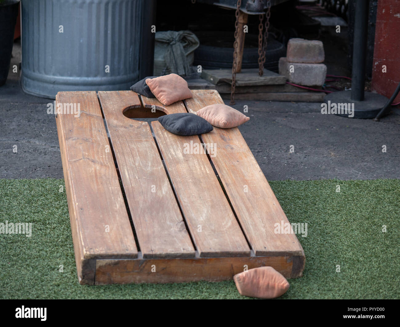 Sets of beanbags in competitive game of cornhole on a lumber platform - Stock Image