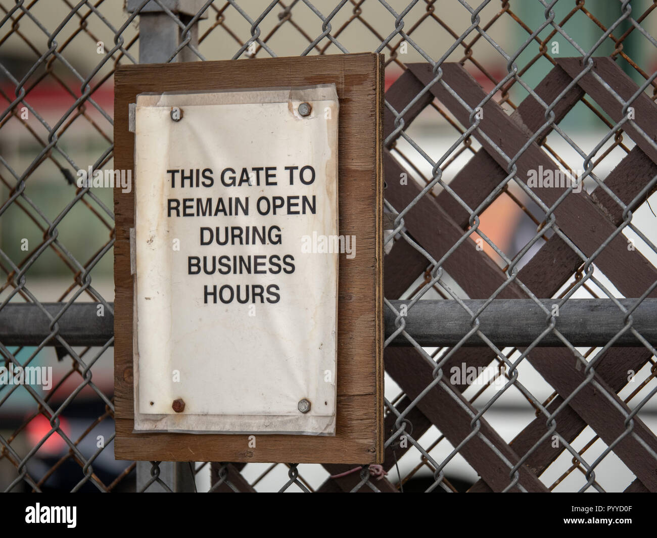 This gate to remain open during business hours paper sign on fence - Stock Image