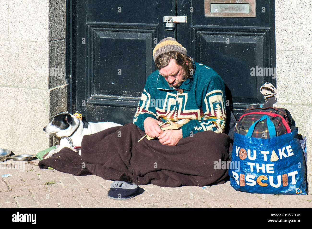 A homeless man and his dog sitting in a doorway. - Stock Image