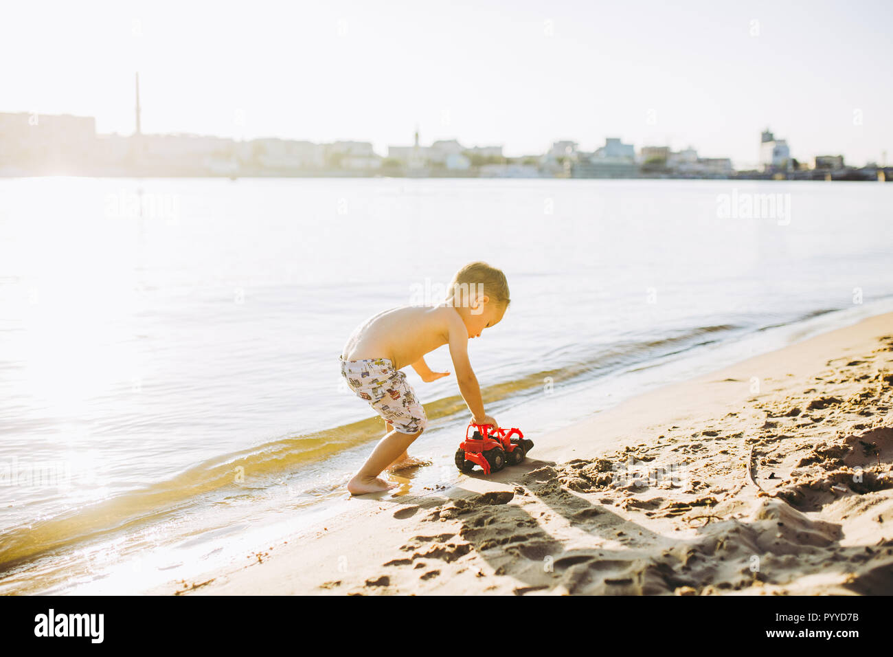 Caucasian child boy plays toy red tractor, excavator on sandy beach by the river in shorts at sunset day - Stock Image