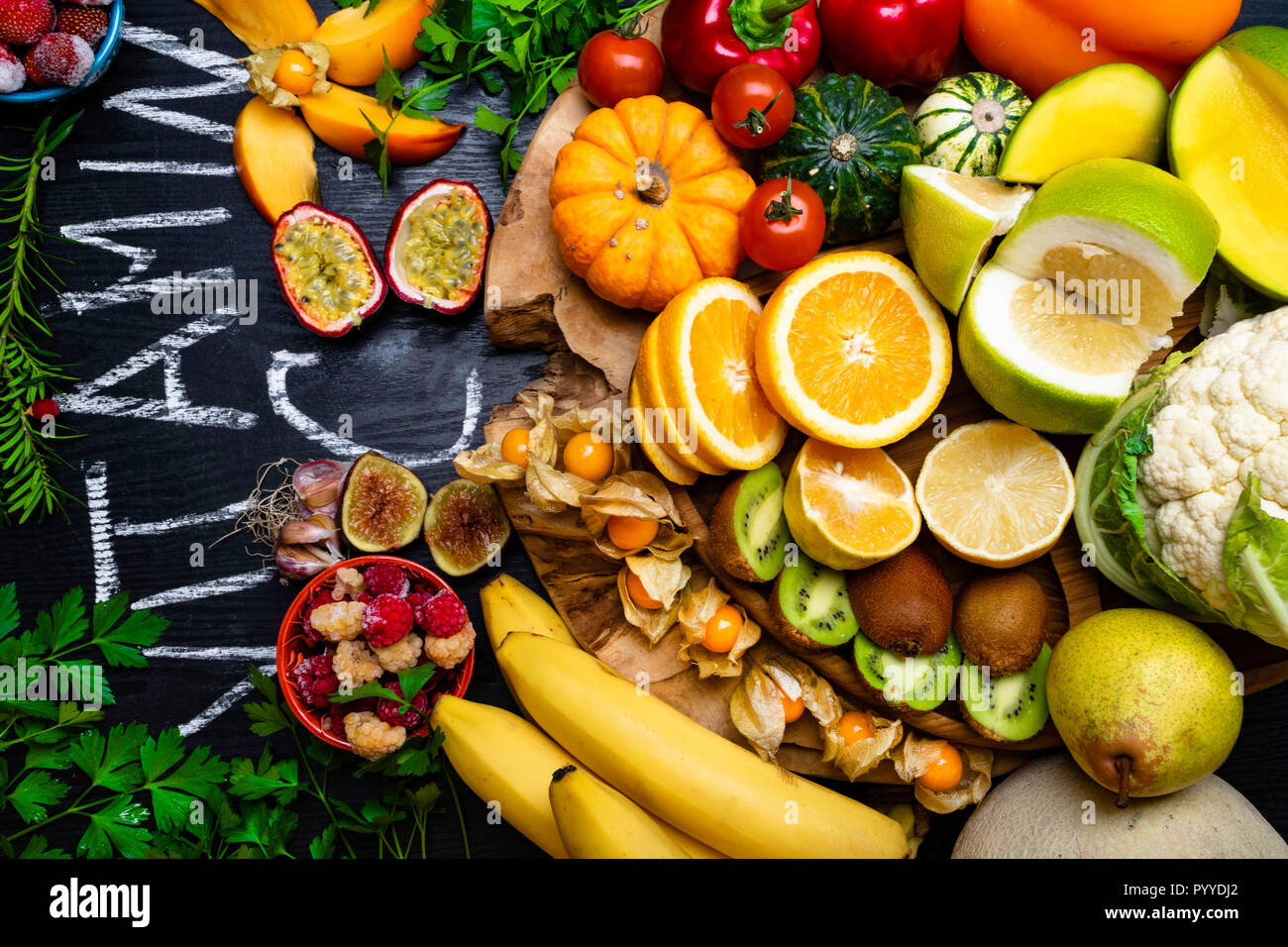 Vitamin C in fruits and vegetables. Natural products rich in vitamin C as oranges, lemons, pepper, kiwi, parsley leaves, garlic, bananas, mango, cabba - Stock Image