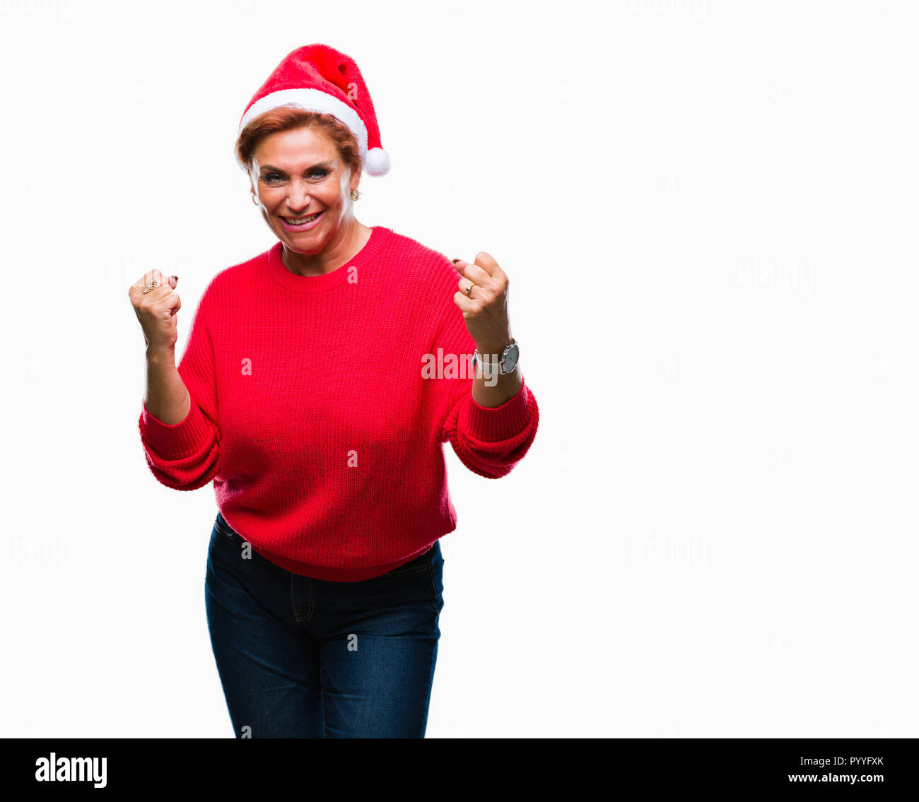 Atrractive senior caucasian redhead woman wearing christmas hat over isolated background very happy and excited doing winner gesture with arms raised, - Stock Image