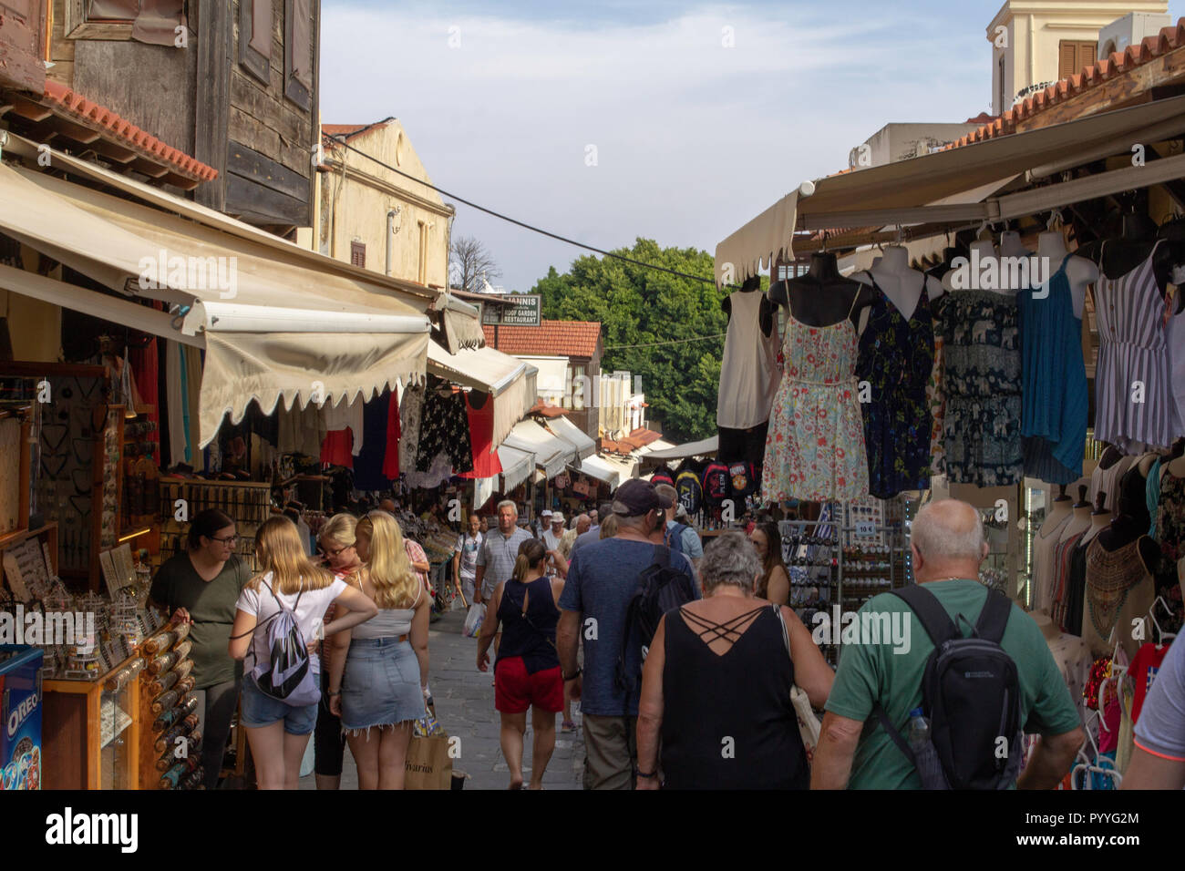 A shopping street in the Old Town of Rhodes. though it is an UNESCO Heritage Site much of the town resembles a thriving bazaar. - Stock Image