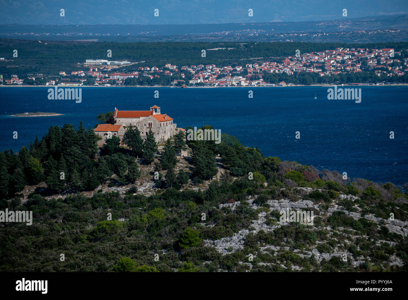 Church and Benedictine Monastery of Saints Cosmas and Damian on the island of Pasman with Sveti Filip i Jakov and Biograd na Moru in the background. - Stock Image