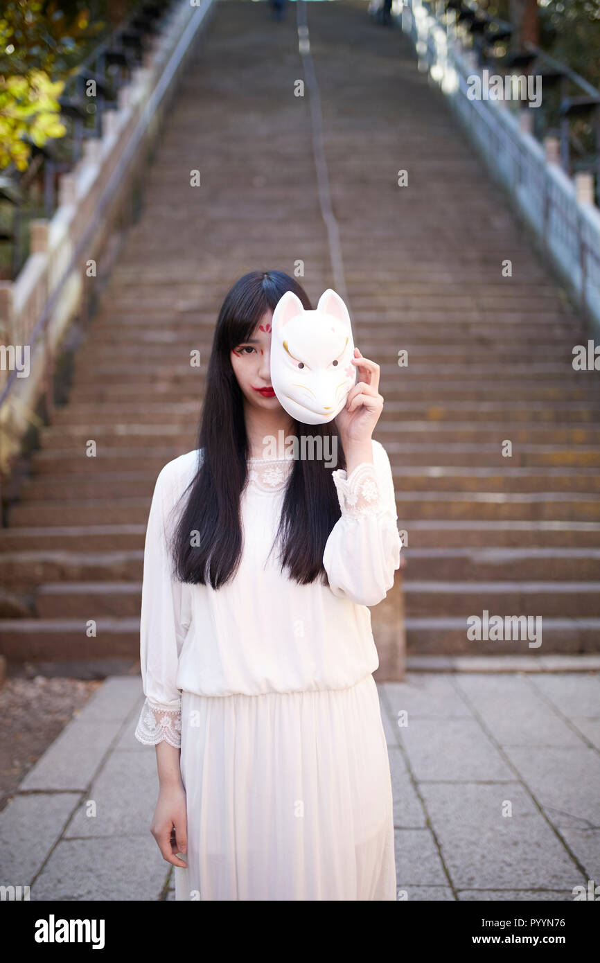 Young Japanese woman with fox mask Stock Photo: 223729498