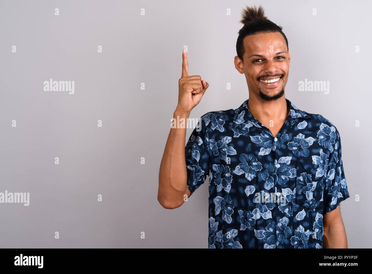 Young bearded handsome African man against gray background - Stock Image