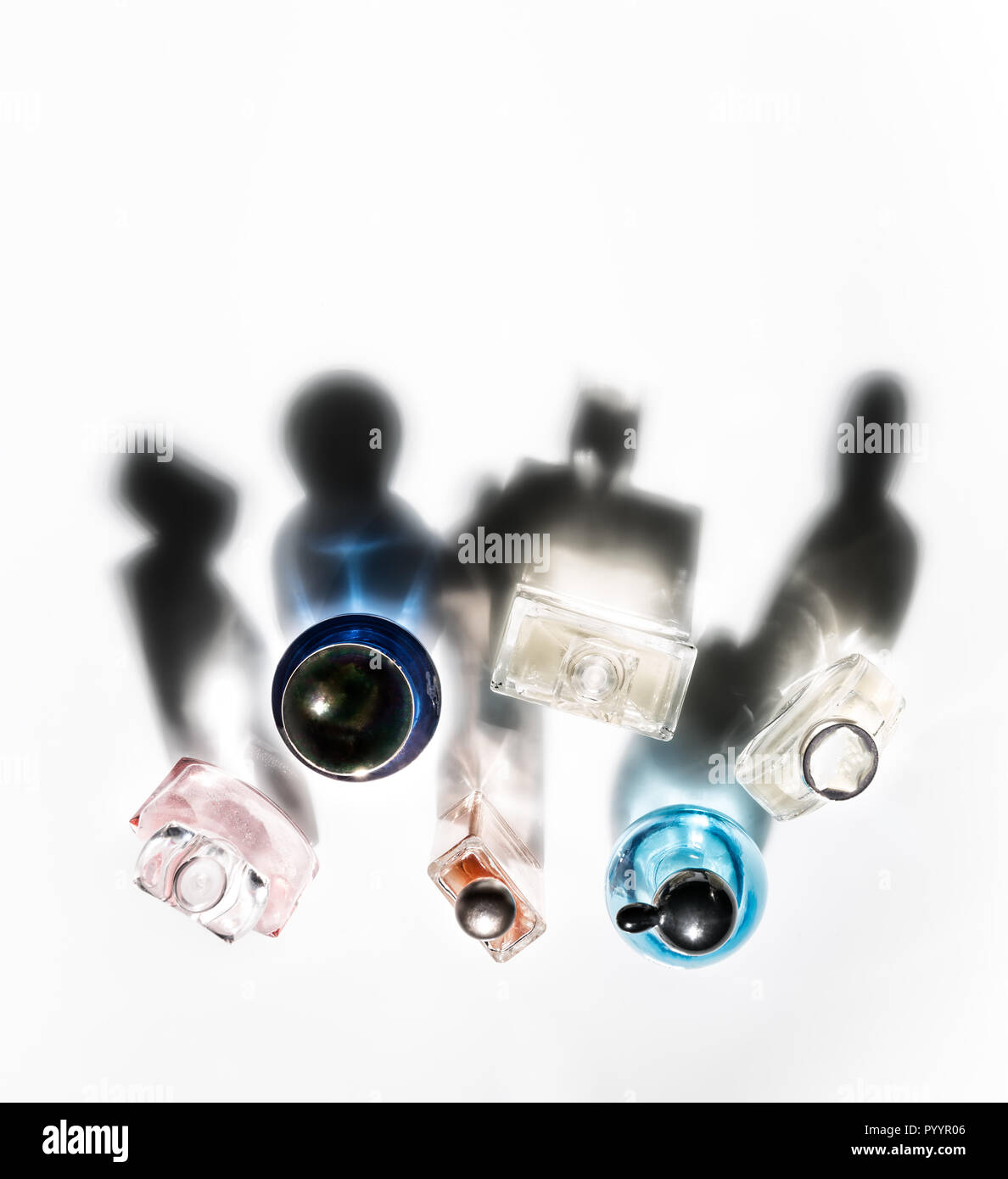 Shadows of perfume bottles in the form of communicating various human characters. - Stock Image