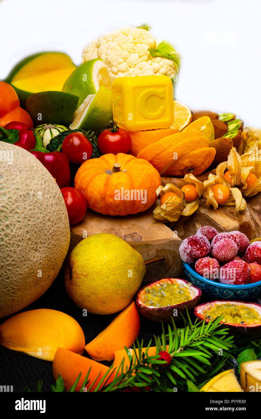 Vitamin C in fruits and vegetables. Natural products rich in vitamin C as needles, oranges, lemons, pepper, kiwi, parsley leaves, garlic, bananas, man - Stock Image