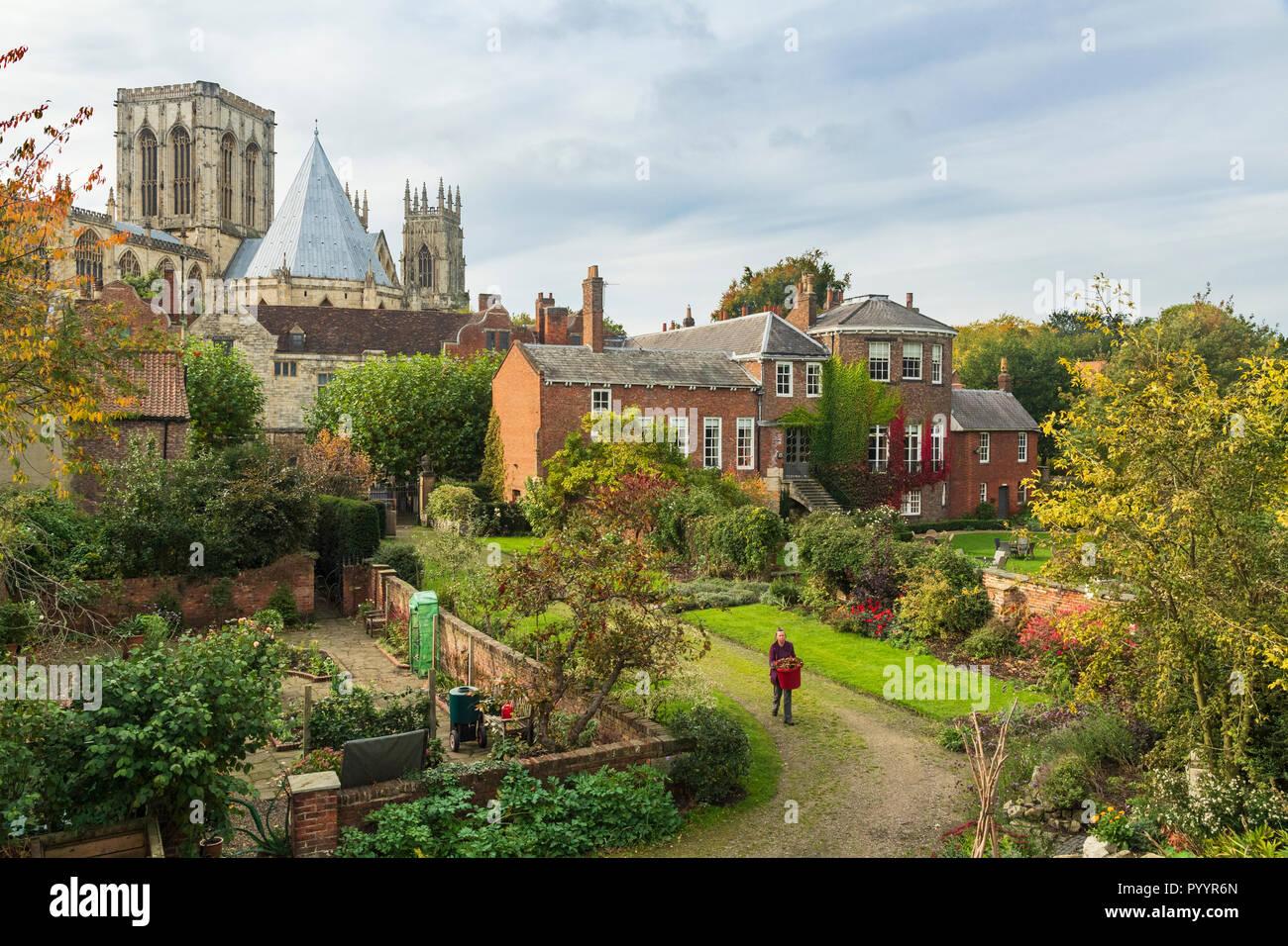 Scenic view of historic buildings from city walls - Grays Court (gardener working) Minster & Treasurer's House - York, North Yorkshire, England, UK. - Stock Image