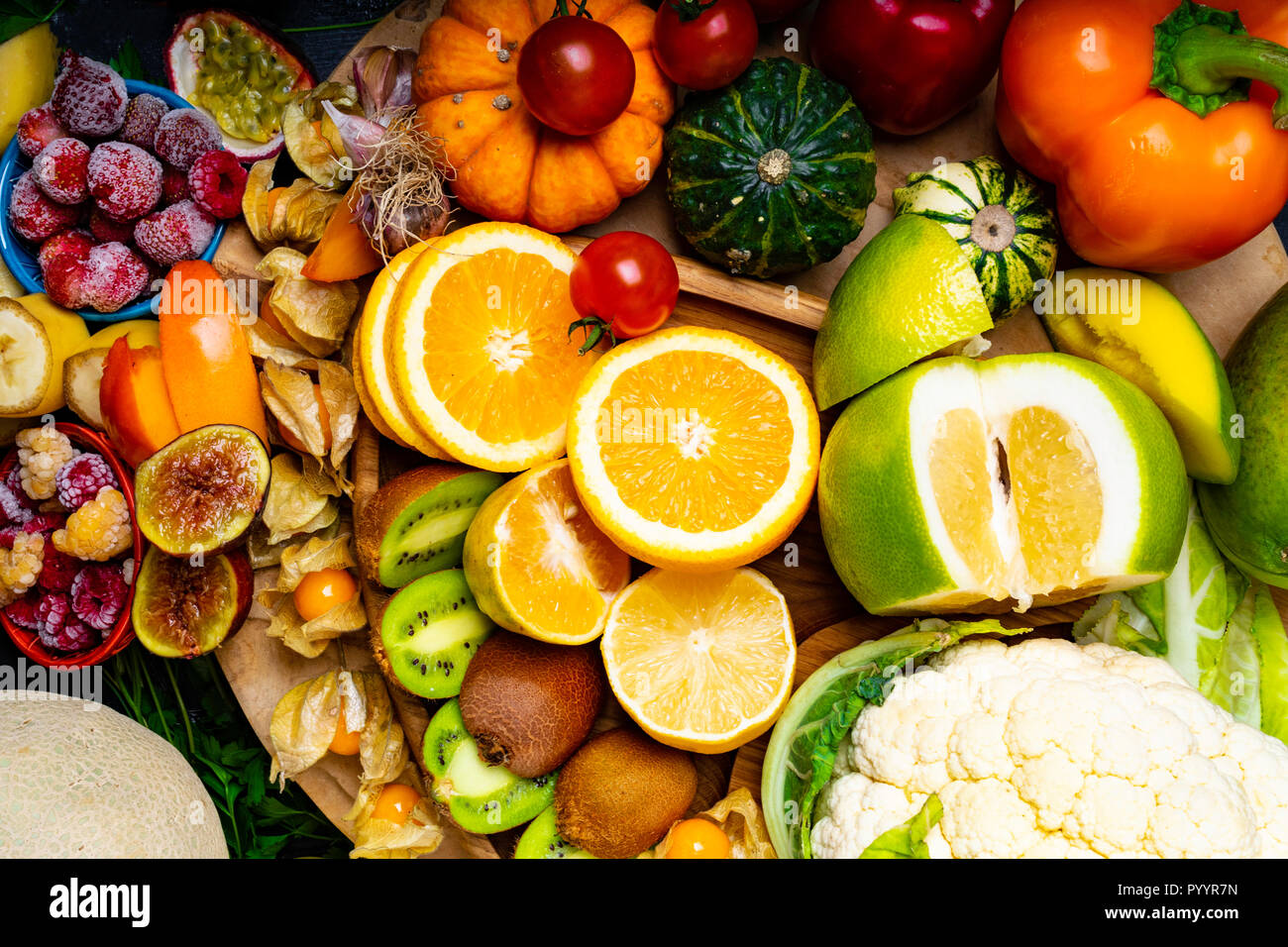 Vitamin C in fruits and vegetables. Natural products rich in vitamins and fiber, as parsley, oranges, lemons, pepper, kiwi, parsley leaves, garlic, ba - Stock Image