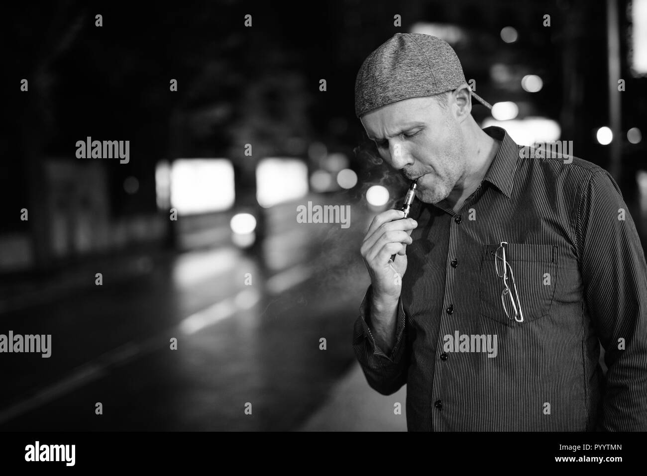 Mature man smoking electronic cigarette in the streets at night  Stock Photo