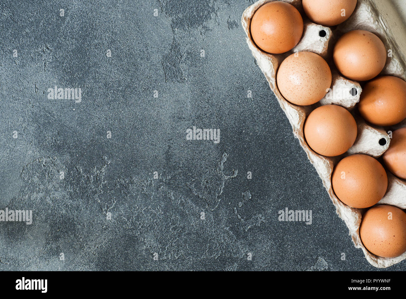 Chicken eggs in a cardboard box on a dark brutal table - Stock Image