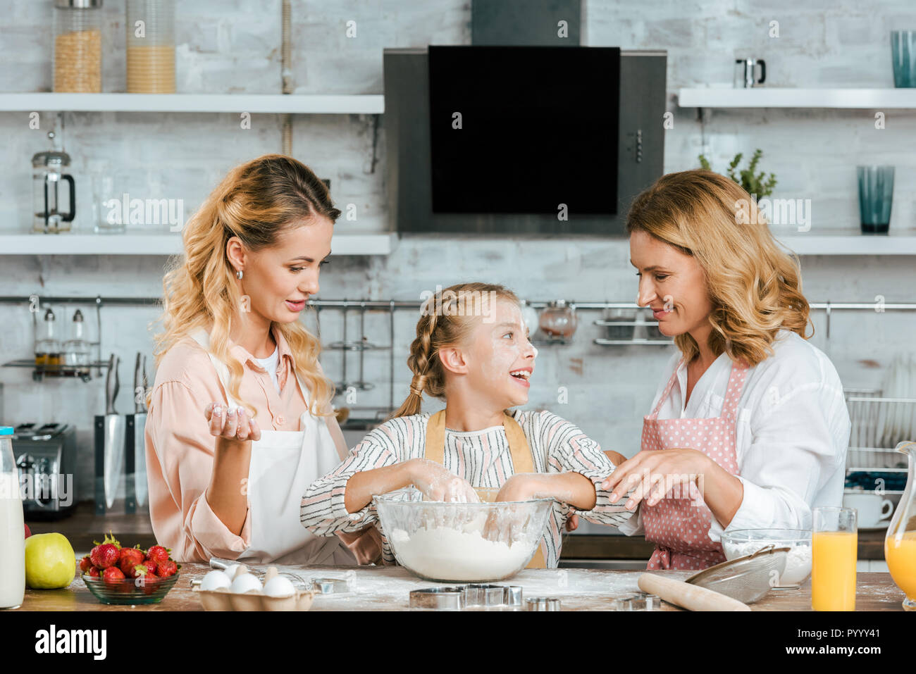 happy little child preparing dough with mother and grandmother at home - Stock Image