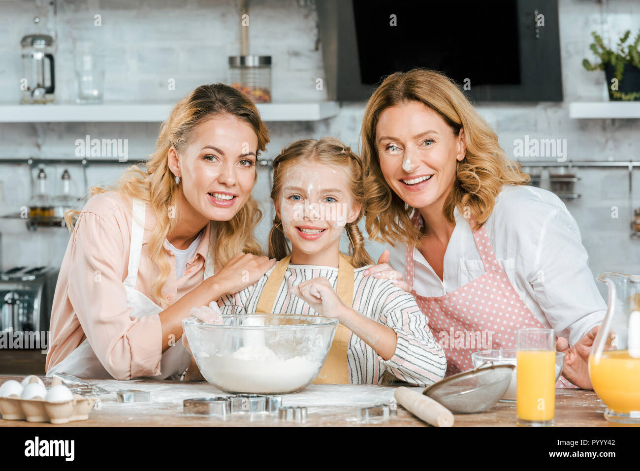 happy little child preparing dough with mother and grandmother at home and looking at camera - Stock Image