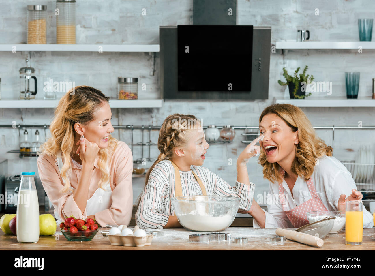 happy little child preparing dough and playing with mother and grandmother at home - Stock Image