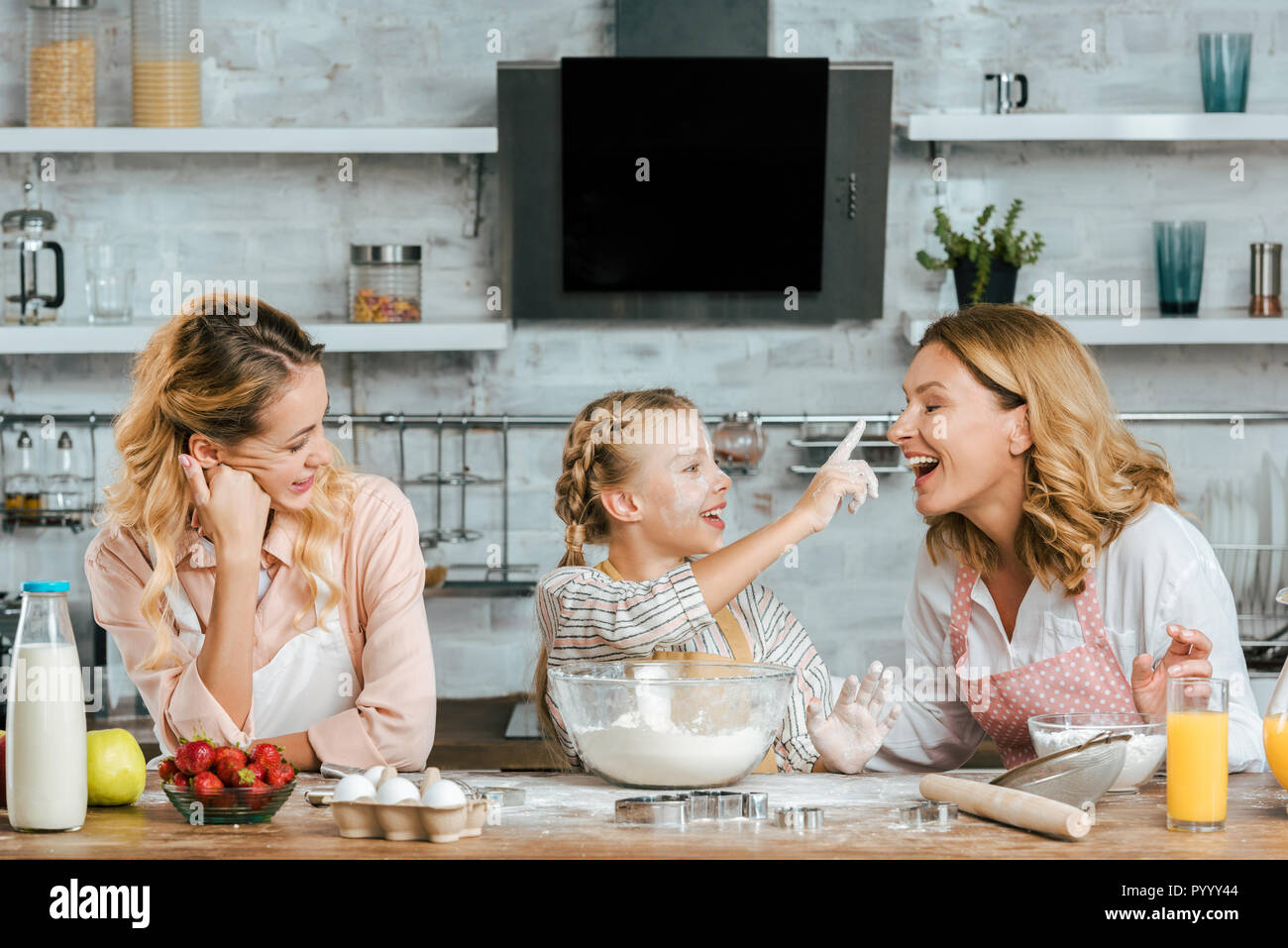 smiling little child preparing dough and playing with mother and grandmother at home - Stock Image