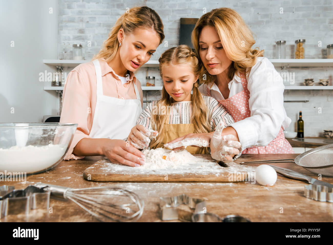 adorable child with mother and grandmother making dough with flour and egg together at home - Stock Image