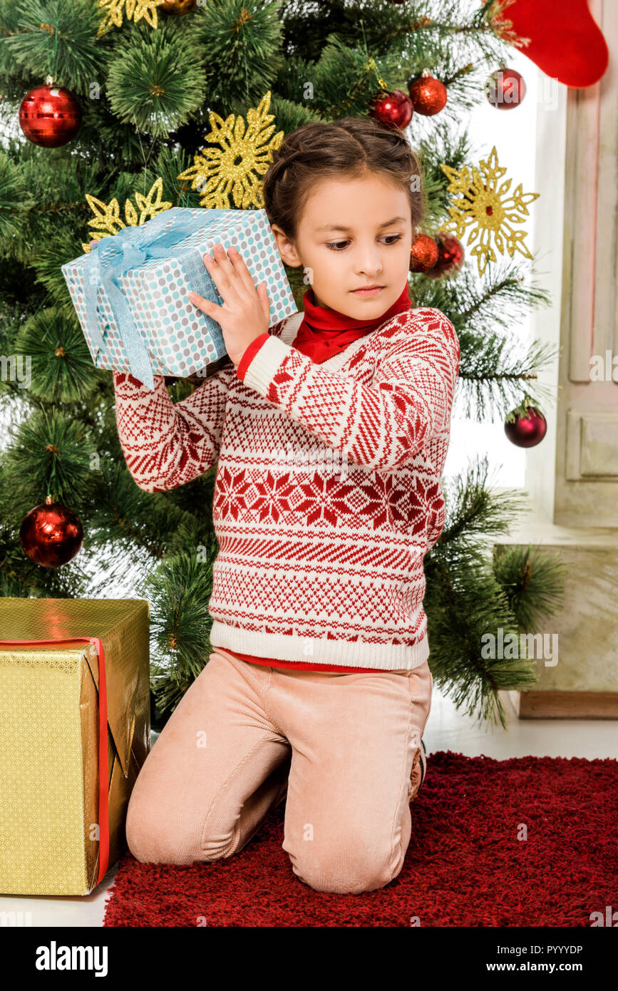 beautiful little kid holding christmas gift in front of christmas ...