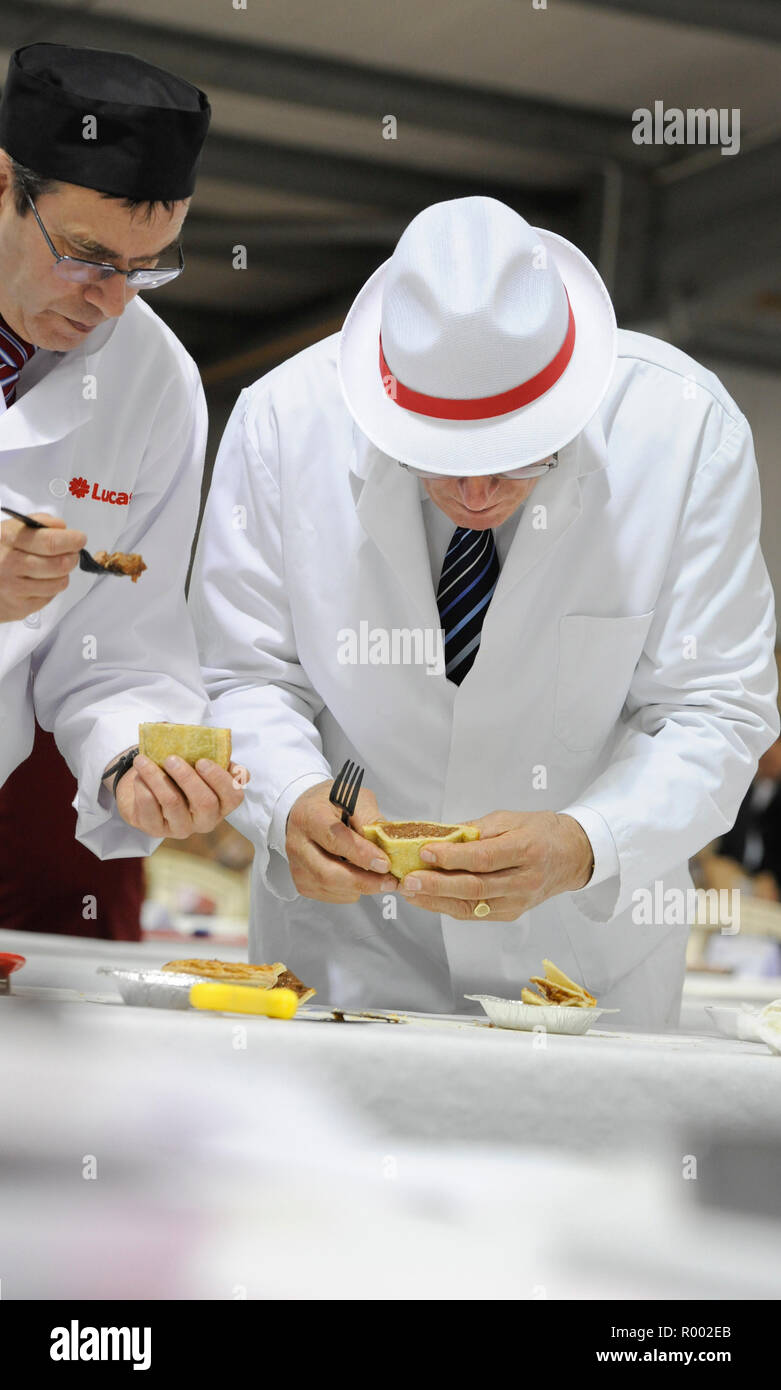 A pair of judges examine pies and other meat produce at a regional competition for producers. Stock Photo