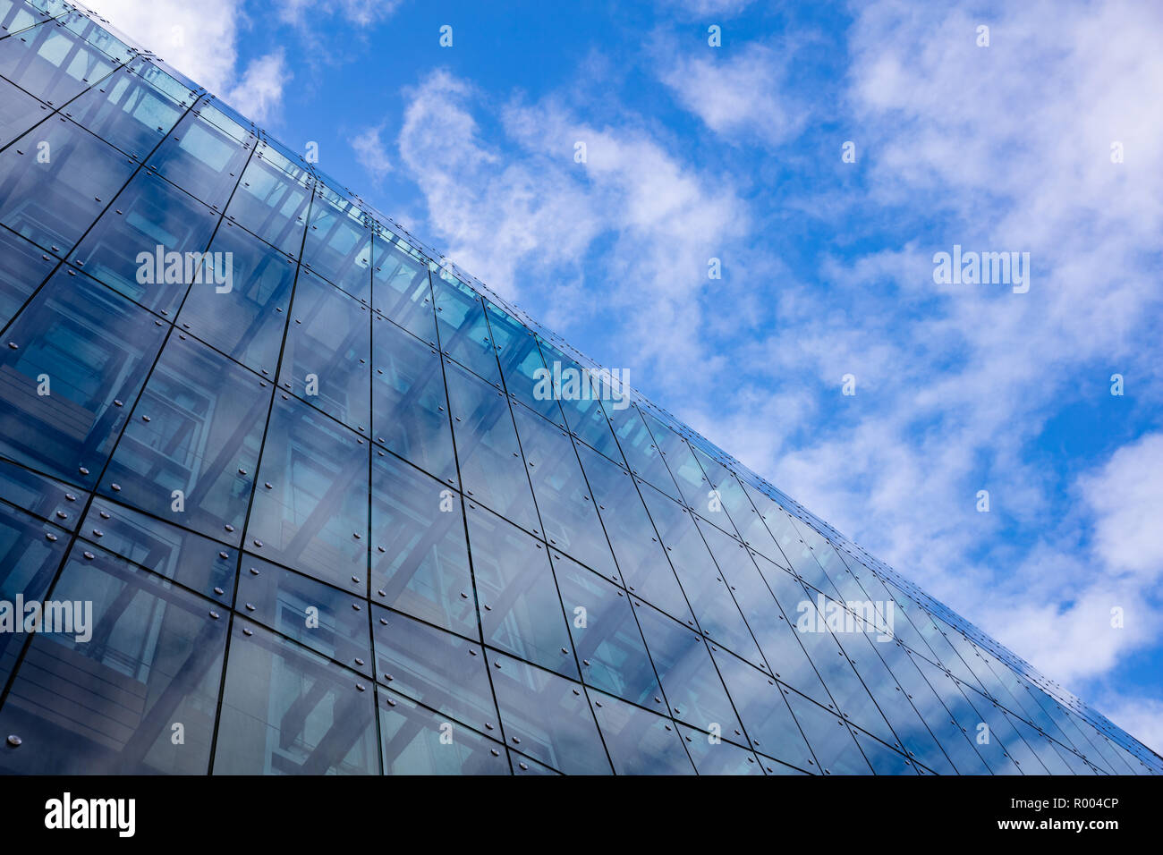 Glass and steel skyscraper multi story office building in Berlin, Germany, low angle, against blue sky background. - Stock Image