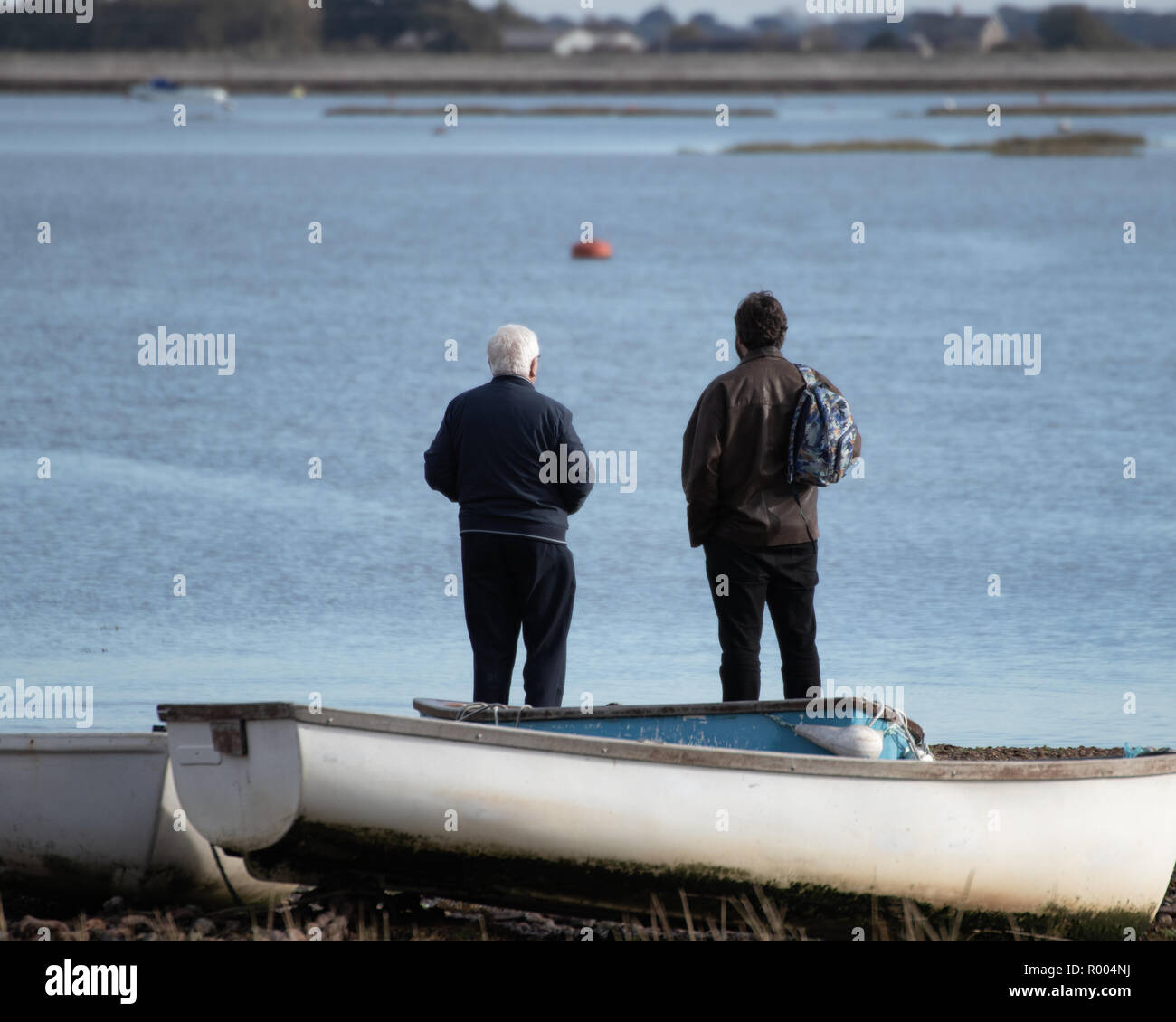 elderly father and grown up son looking out to see at the coast with an old wooden boat in the foreground - Stock Image