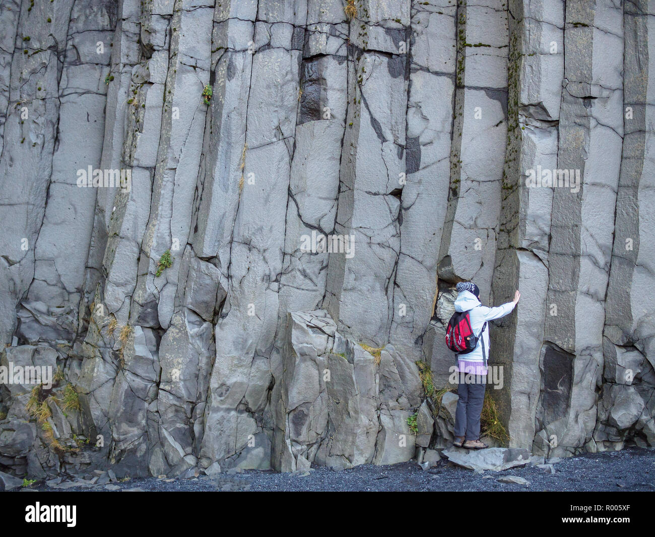 Tourist girl at stacks of basalt rock on the cliffline Reynisfjall, Iceland - Stock Image