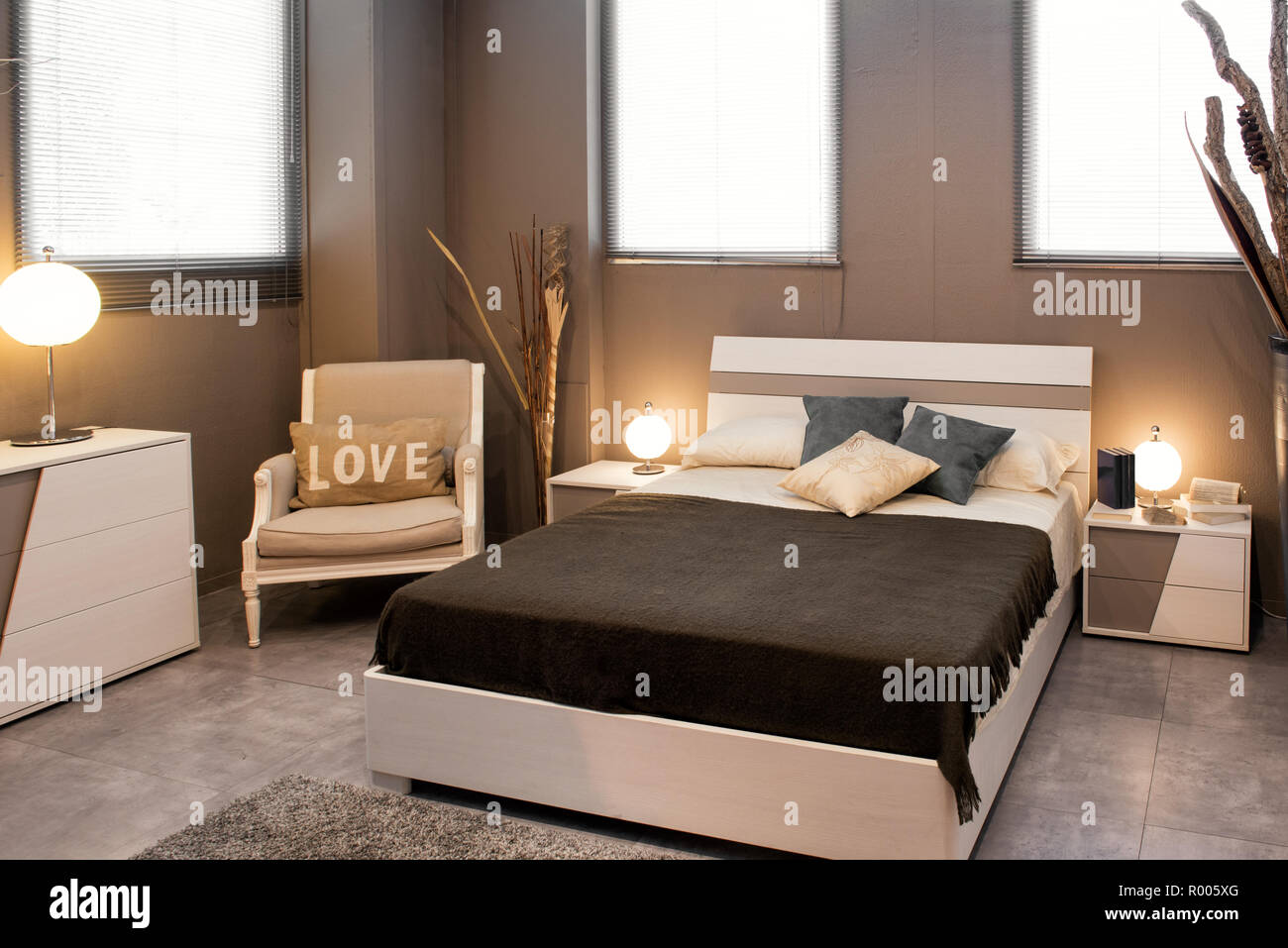 Romantic Brown Luxury Bedroom Interior With Divan Style Bed And Chair With Love Cushion Illuminated By Round Lamps Stock Photo Alamy