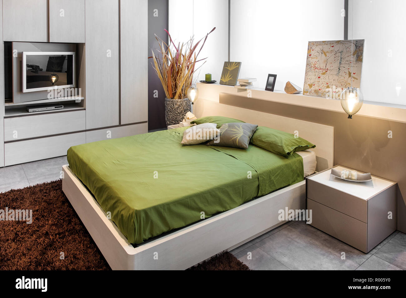 Modern bedroom design with high double bed with green linens and brown carpet on the floor - Stock Image