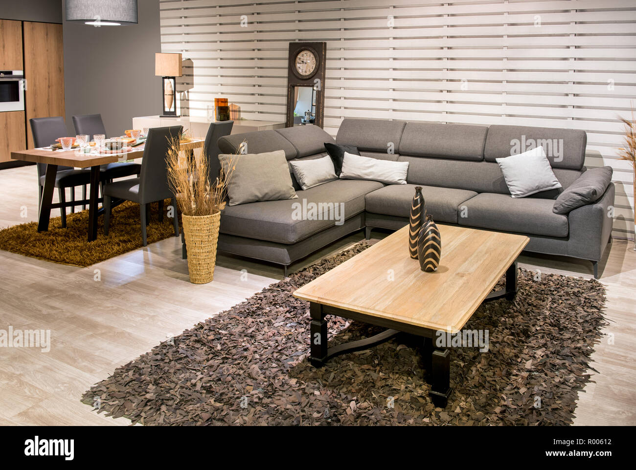 Spacious open plan kitchen dining room and living room interior with grey upholstered lounge suite rug set table and wooden floor in a modern house