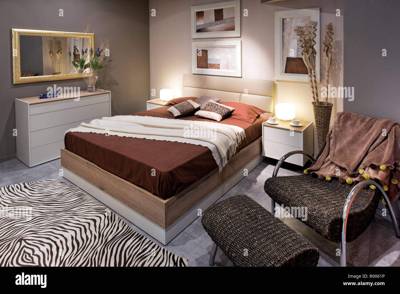 Double Bedroom Design Concept With High Brown Bed And Comfortable Armchair With Ottoman Zebra Carpet On The Floor And Paintings On The Walls Stock Photo Alamy