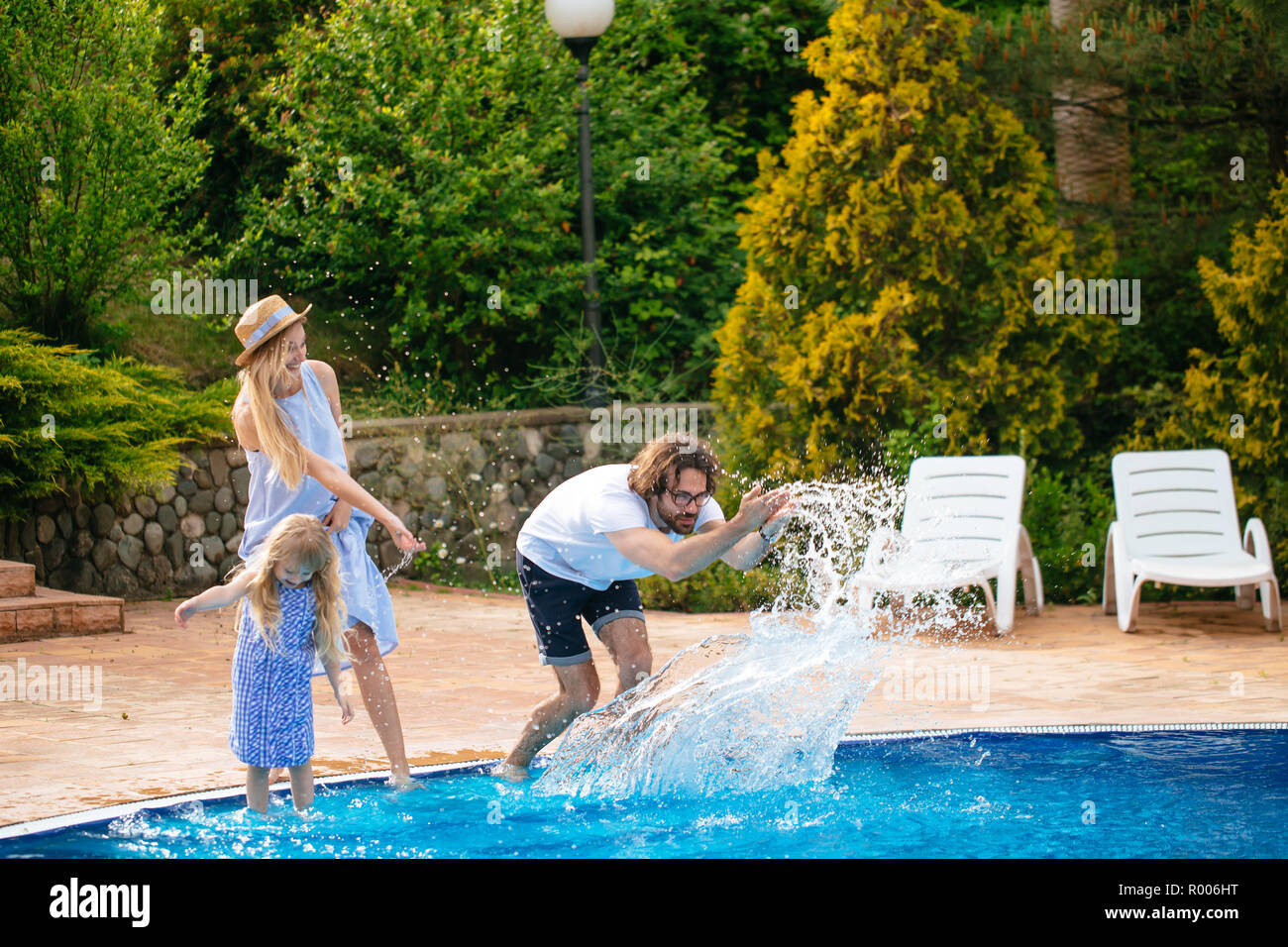 family having fun their pool. family splashing water with legs or hands in swimming pool - Stock Image