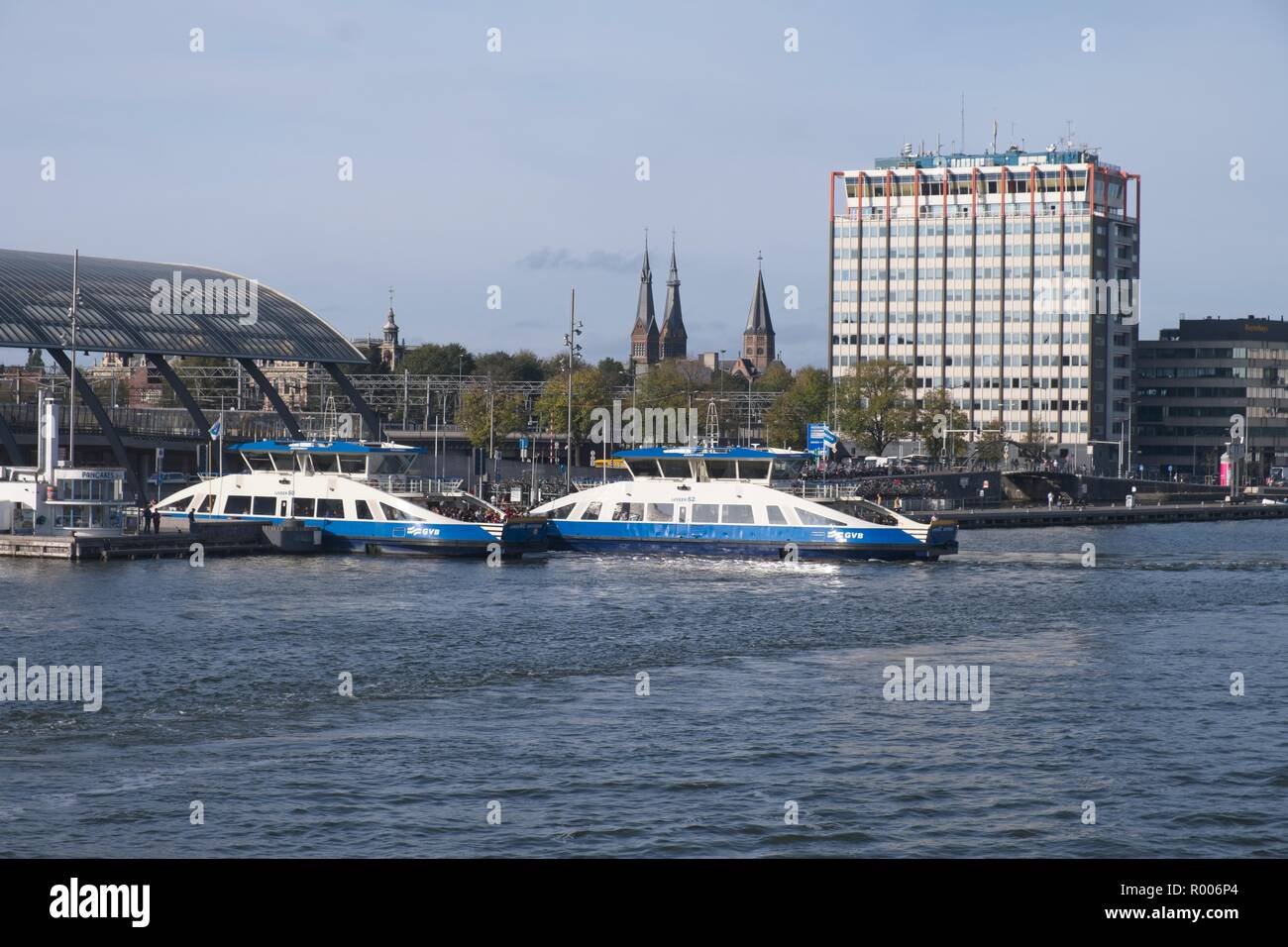 PASSENGER FERRIES MOORED ON THE SOUTH BANK OF THE IJ IN PREPARATION FOR CARRYING PASSENGERS ACROSS TO THE NORTH BANK, AMSTERDAM, THE NETHERLANDS - Stock Image