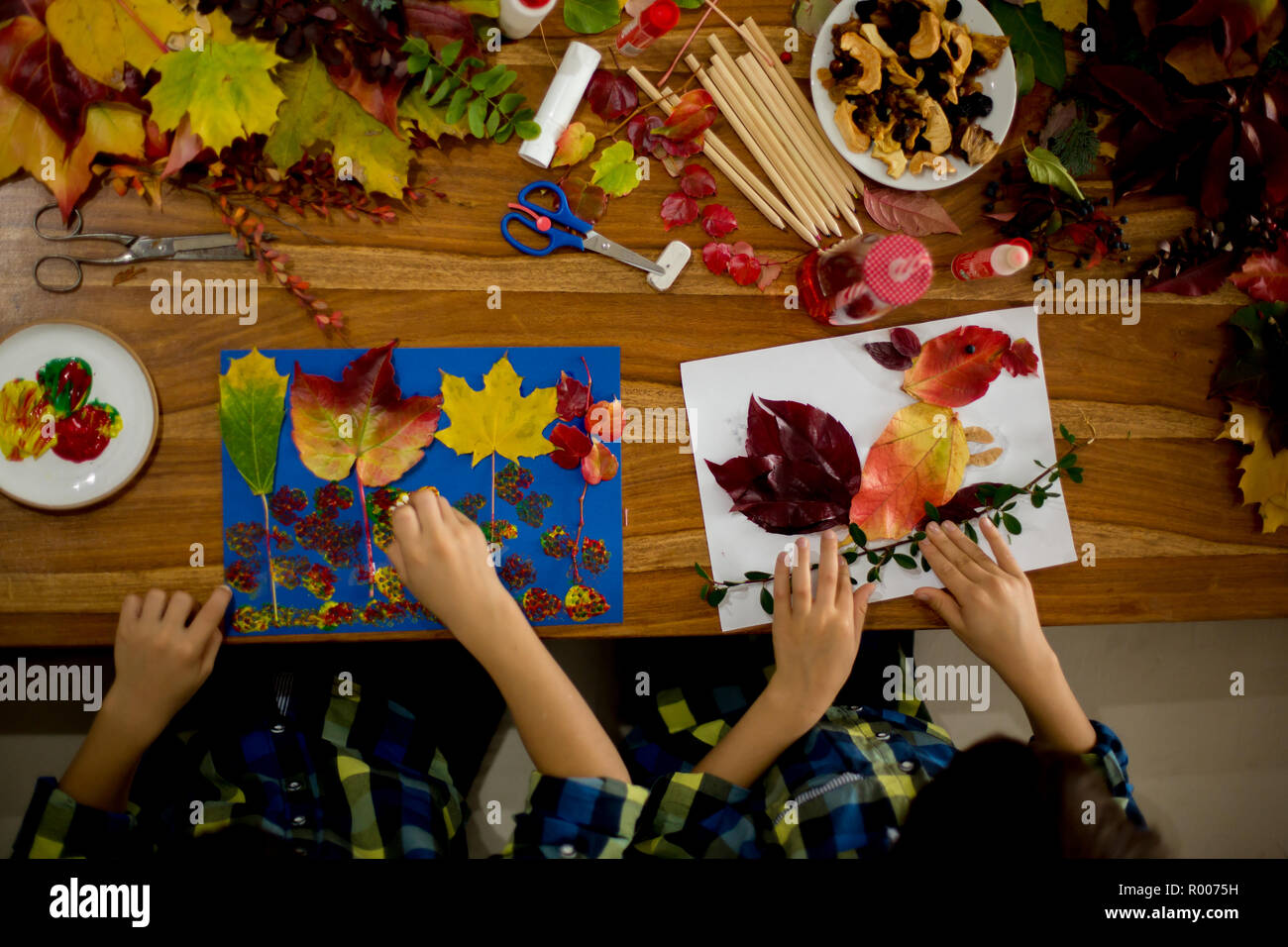 Children, applying leaves using glue, scissors, and paint, while doing arts and crafts in school, autumntime - Stock Image