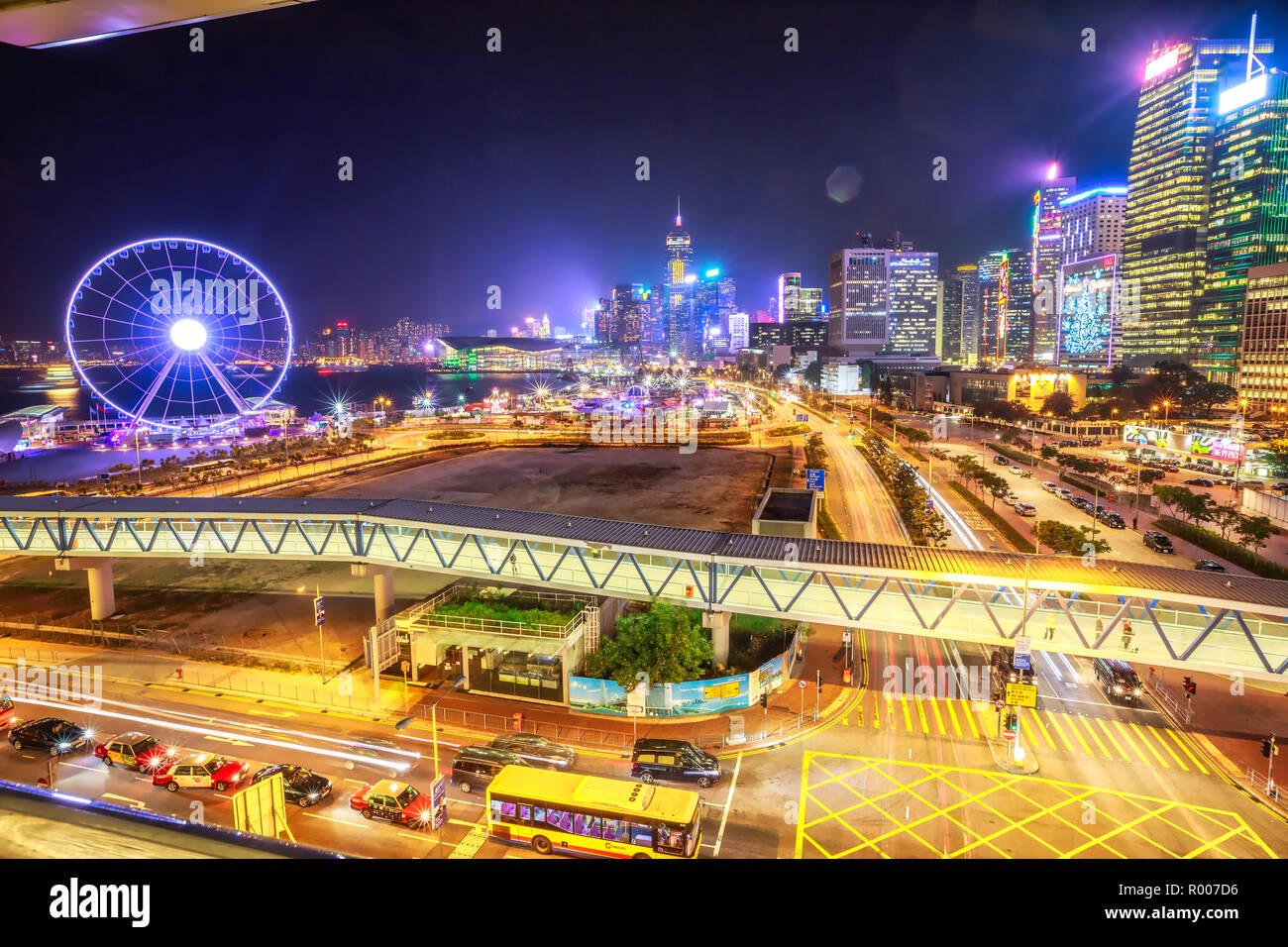 Hong Kong, China - Jannuary 23, 2017: Scenic aerial view of cityscape in Hong Kong, Central District, with Observation Ferris Wheel at Victoria Harbour illuminated at night. Urban night city for asian traveler destination. - Stock Image