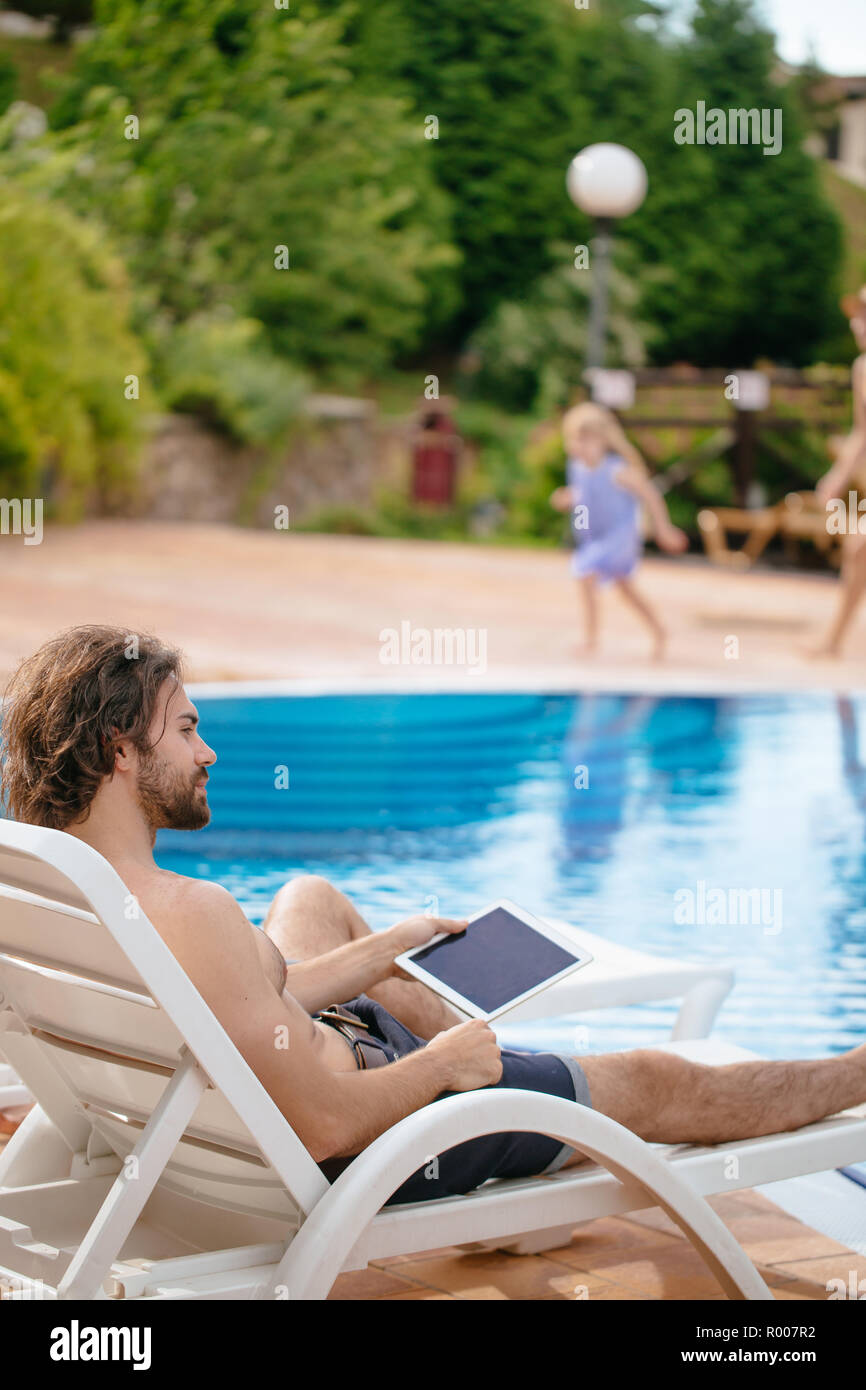 businessman resting on sunbed near swimming pool while working remotely at laptop computer connected to wireless internet - Stock Image