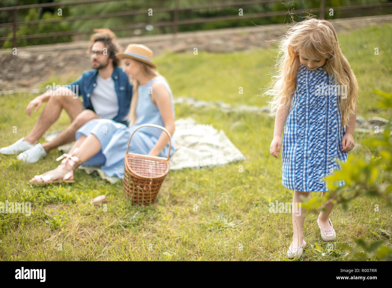 happy Family picnicking outdoors with their cute daughter, blue clothes, woman in hat - Stock Image