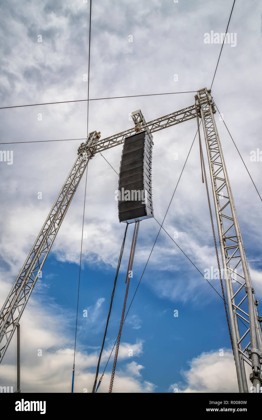Set of powerful speakers hanging over the stage. Daylight shot - Stock Image
