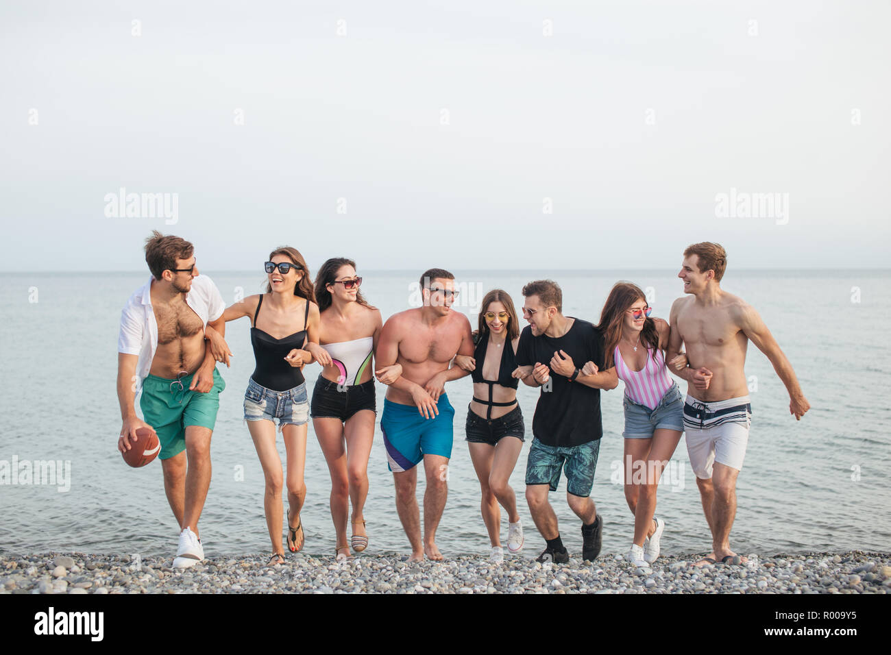 group of friends walking at beach having fun womans piggyback on mans funny vacation R009Y5 - Free funny vacation photos