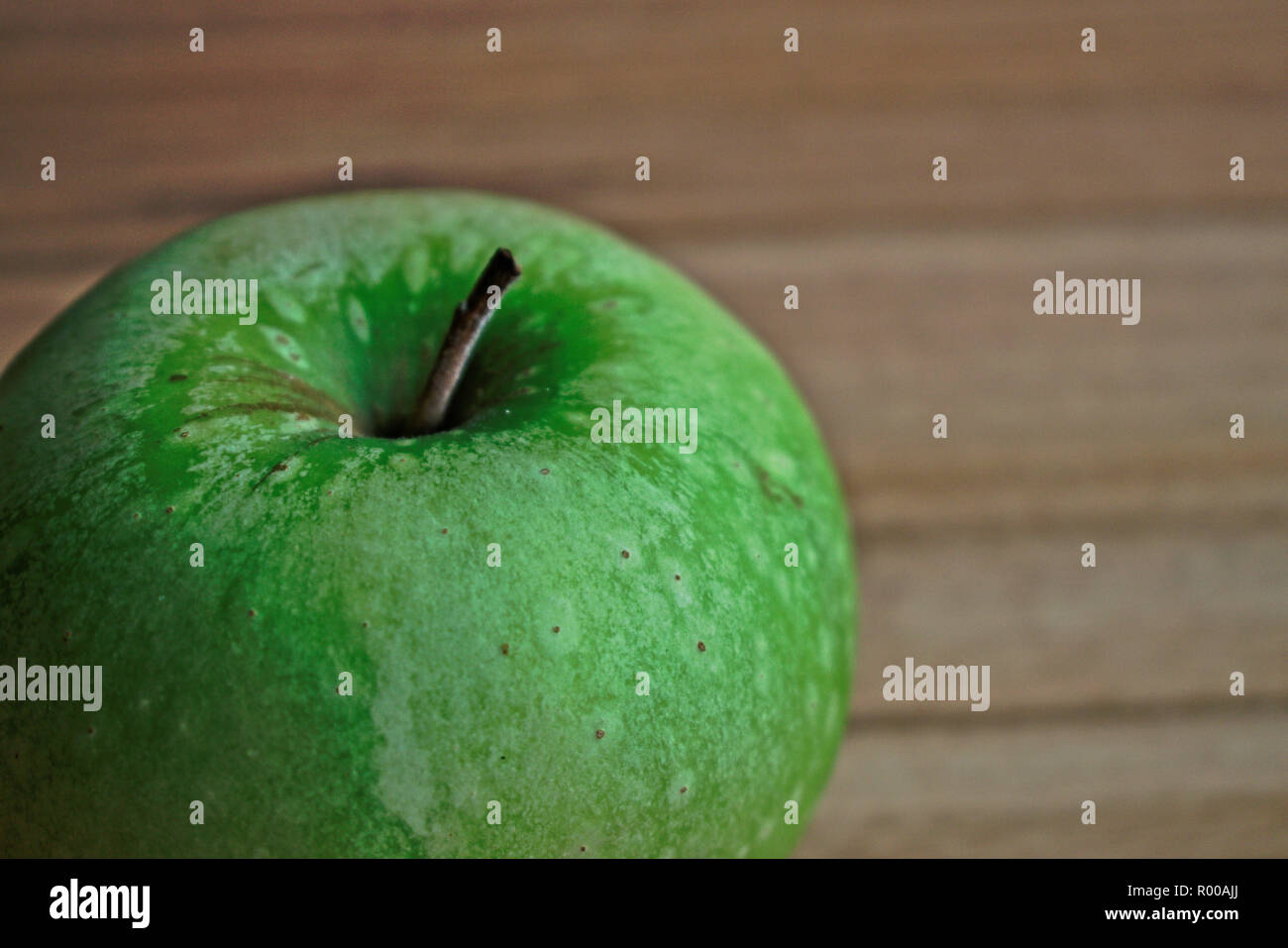 Closeup of an apple on a wooden table - Stock Image