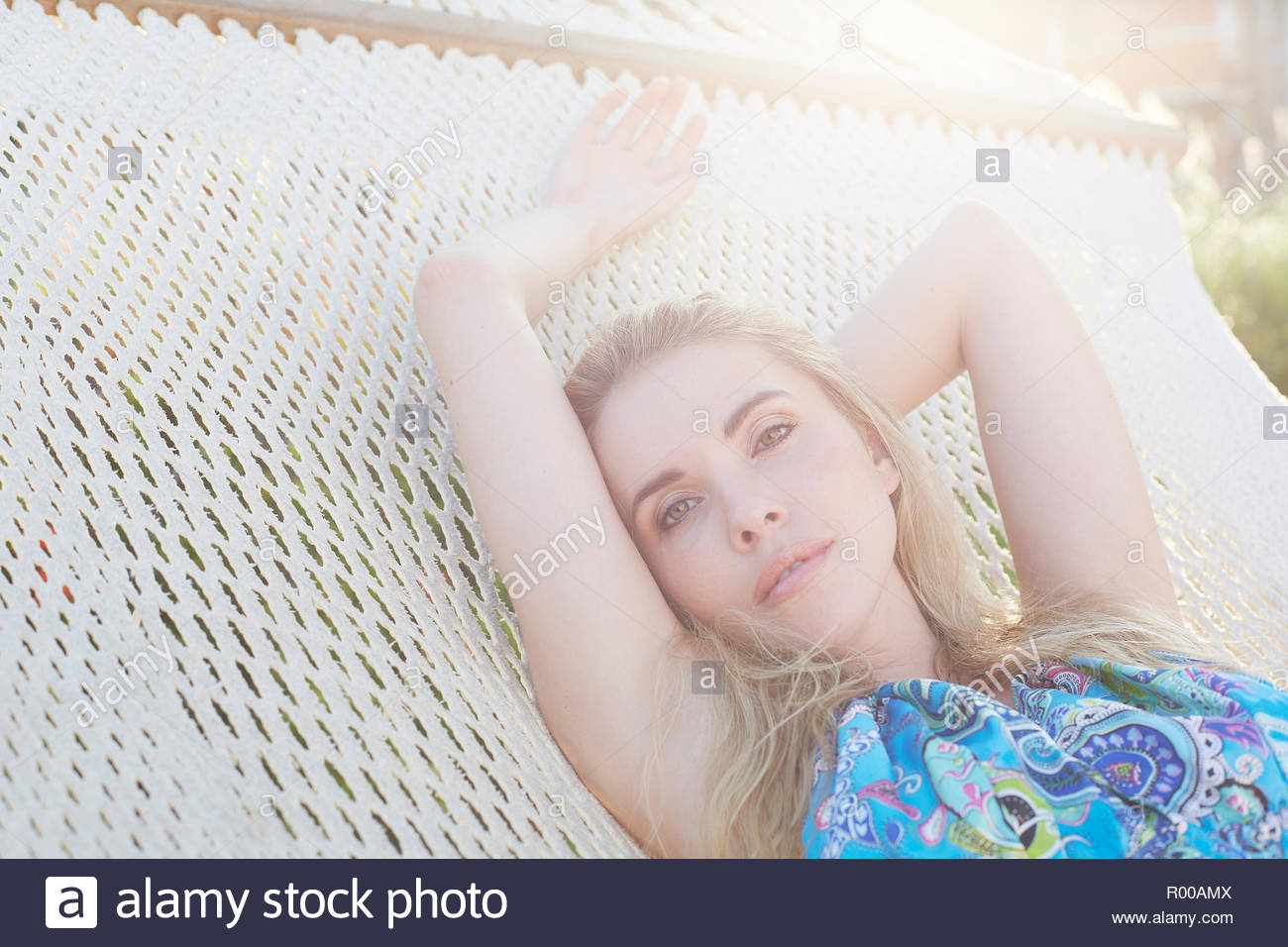 Blond haired young woman lying on hammock - Stock Image
