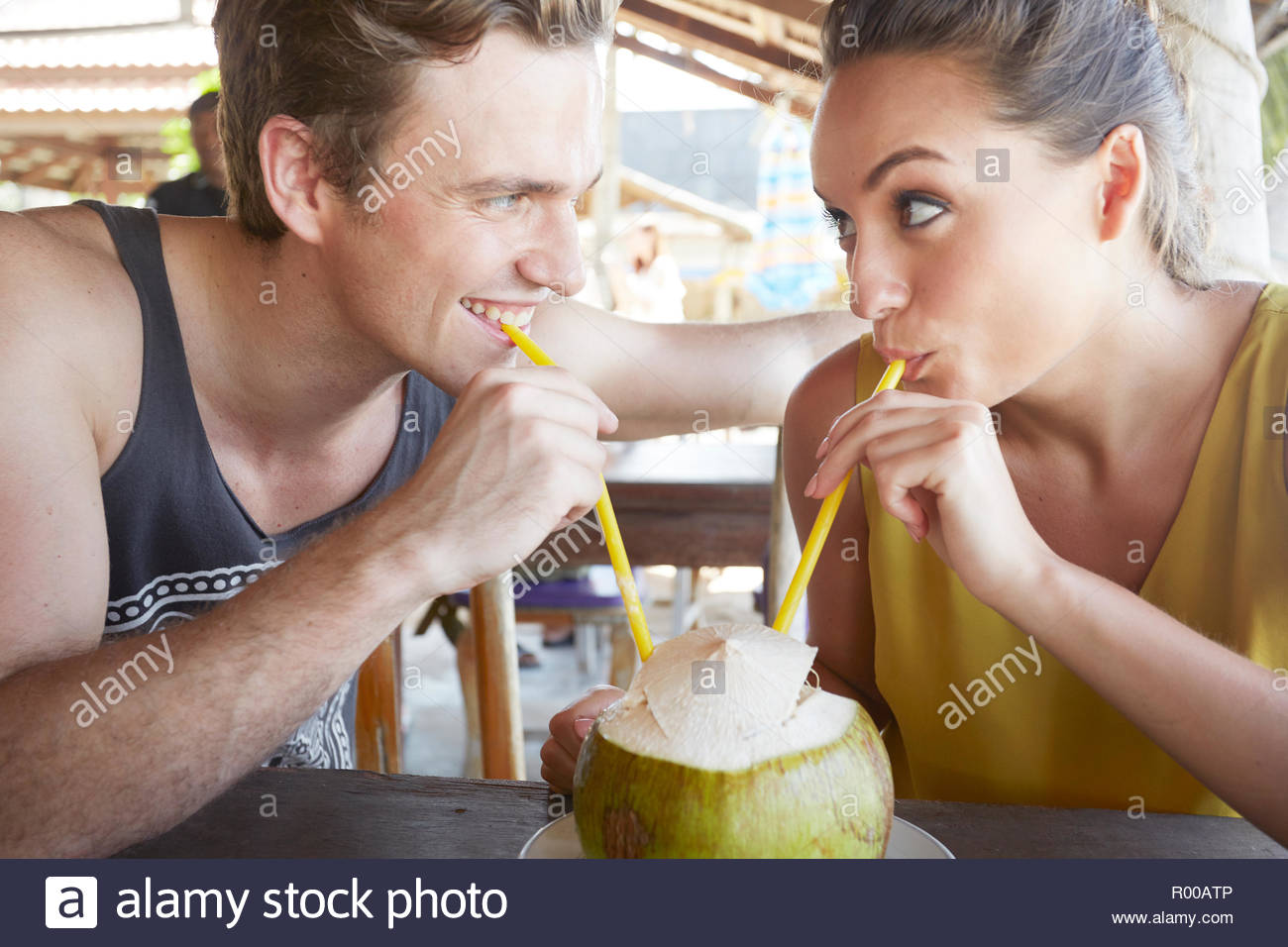 Young couple drinking from coconut with straws Stock Photo