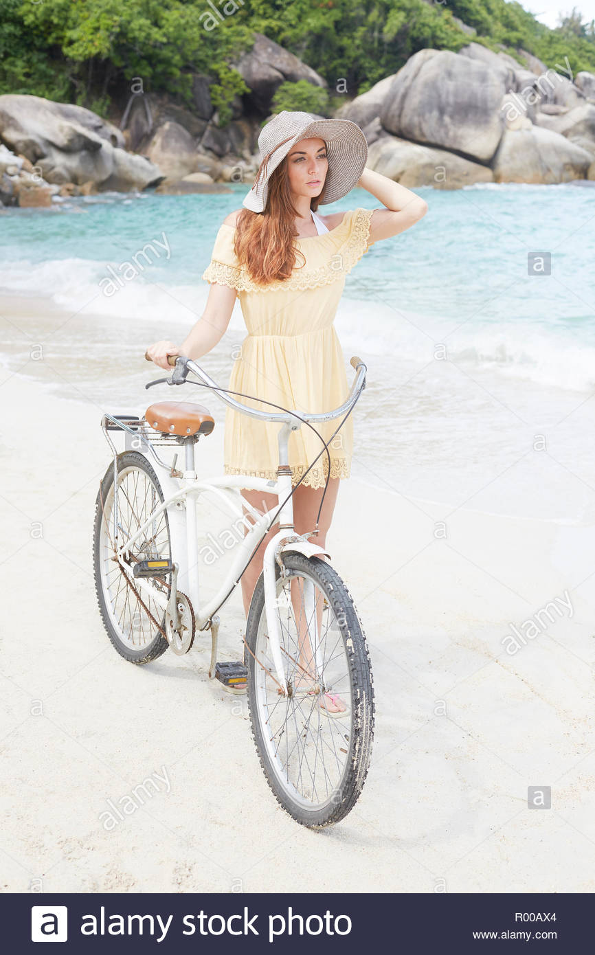 Young woman wearing yellow dress with bicycle on beach Stock Photo