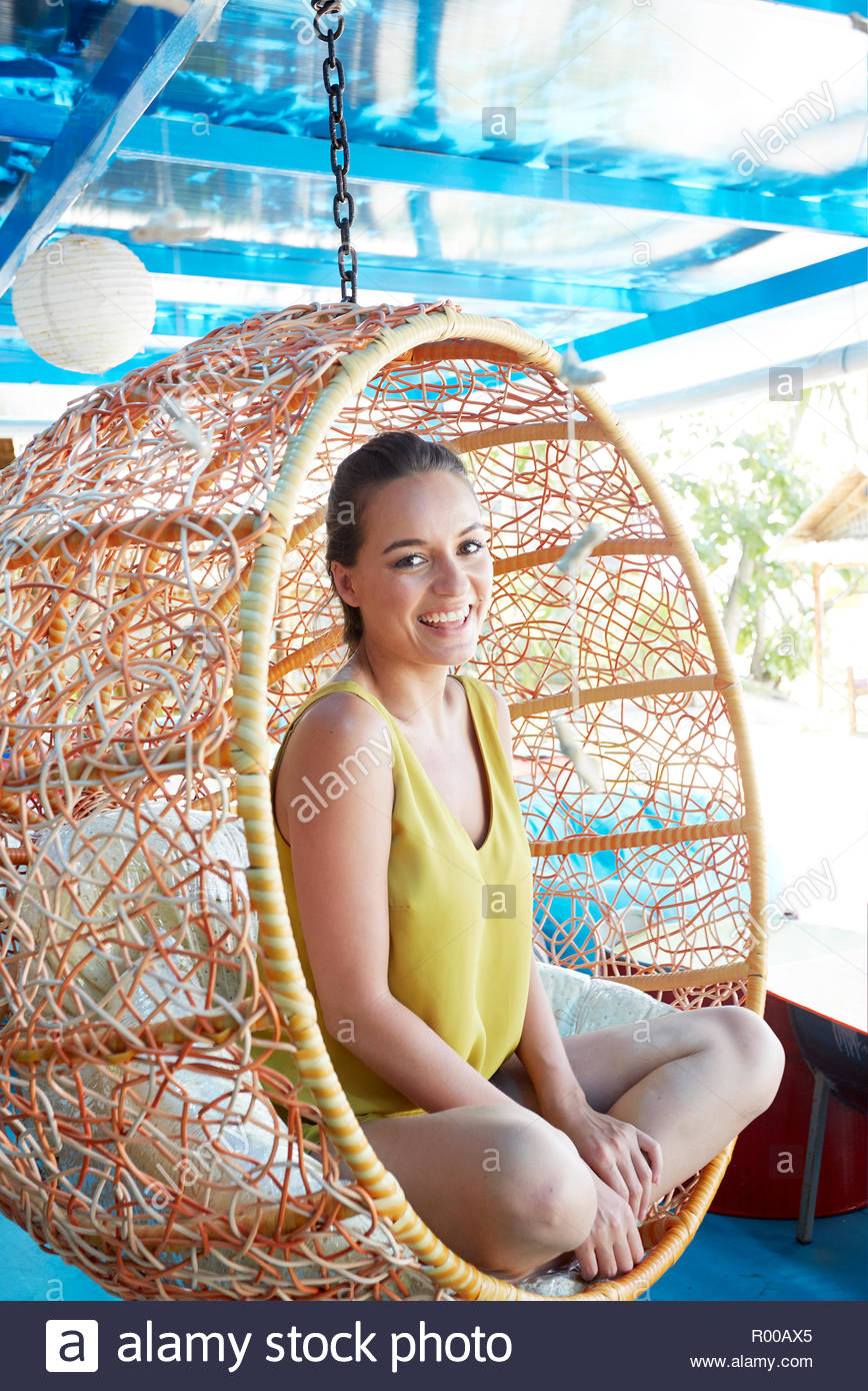 Young woman sitting on hanging spherical chair Stock Photo