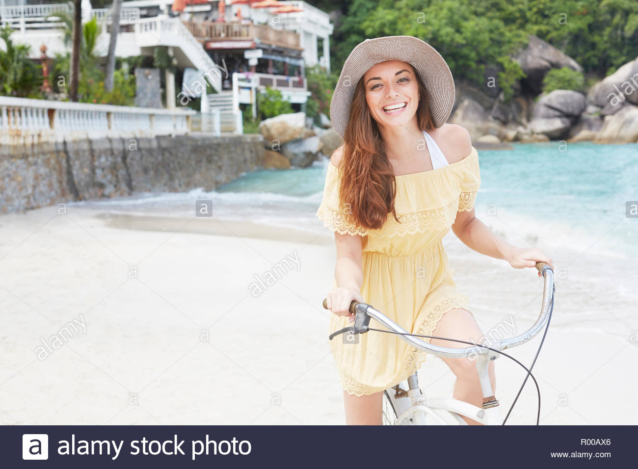 Young woman wearing yellow dress riding bicycle on beach Stock Photo