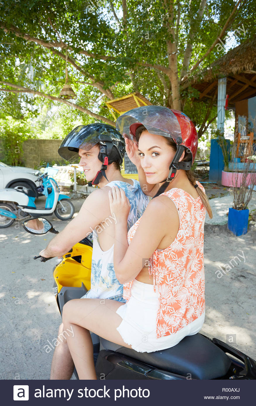 Young man and woman riding moped Stock Photo