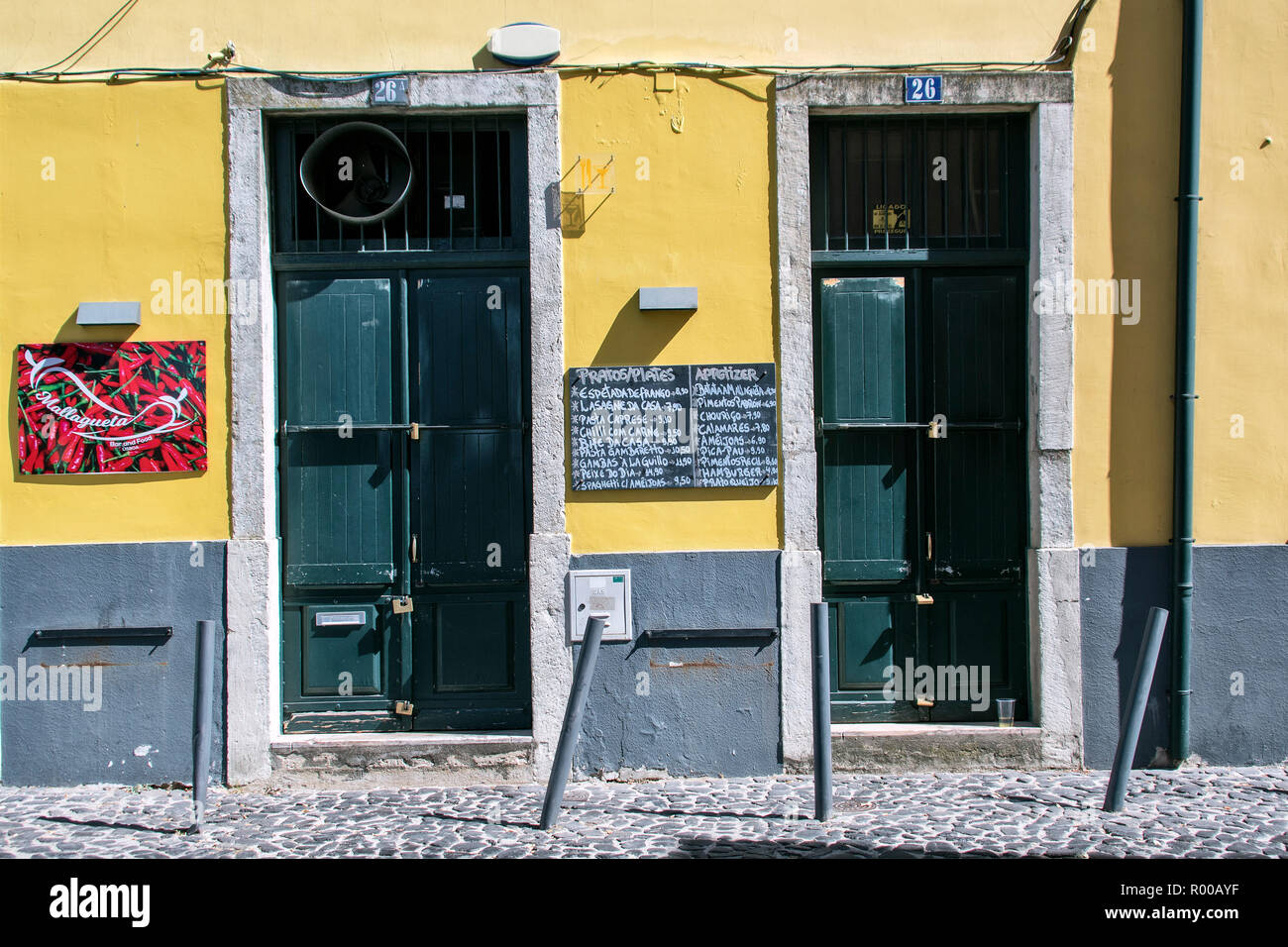 Yellow building facade with menu and closed doors in the Alfama district, Lisbon, Portugal. - Stock Image