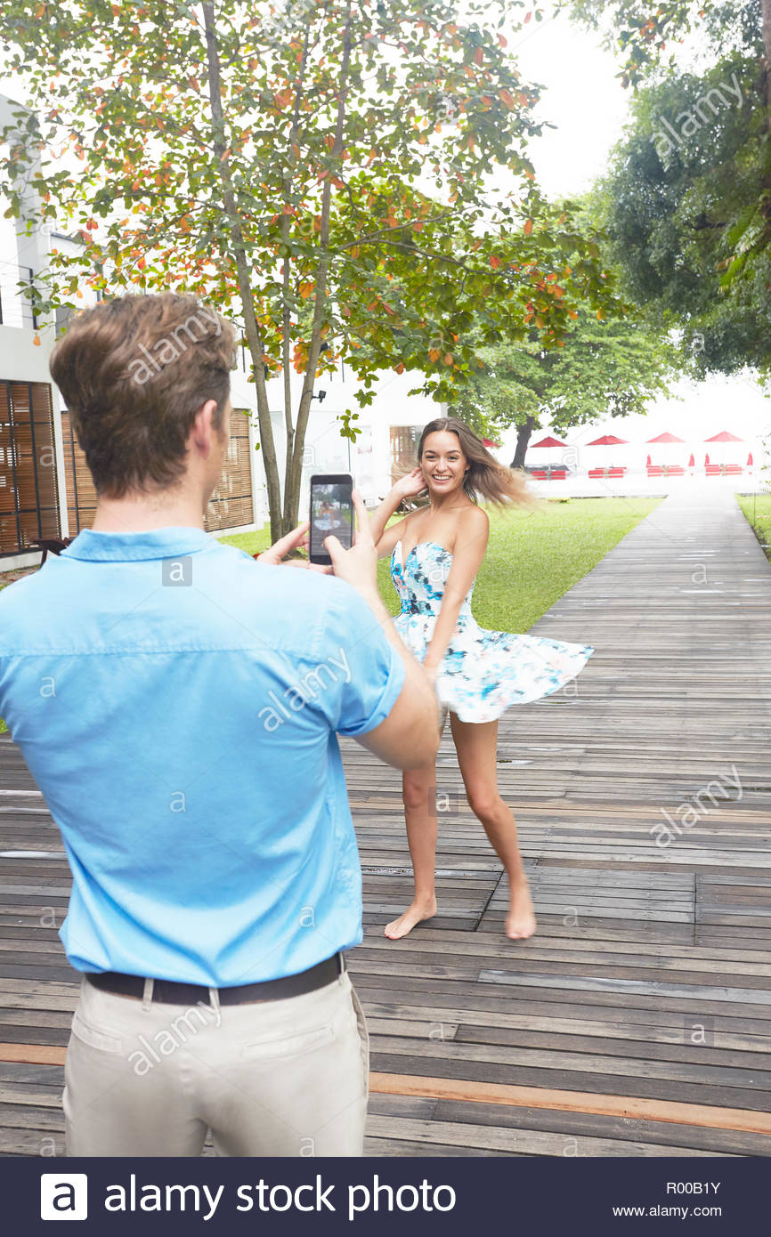 Young man taking photograph of young woman on boardwalk Stock Photo