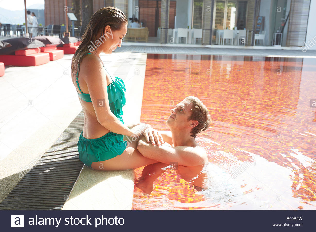 Young couple in orange swimming pool Stock Photo