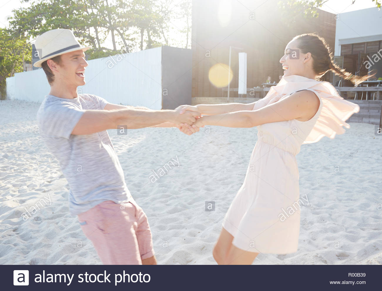 Young couple holding hands while spinning on beach Stock Photo